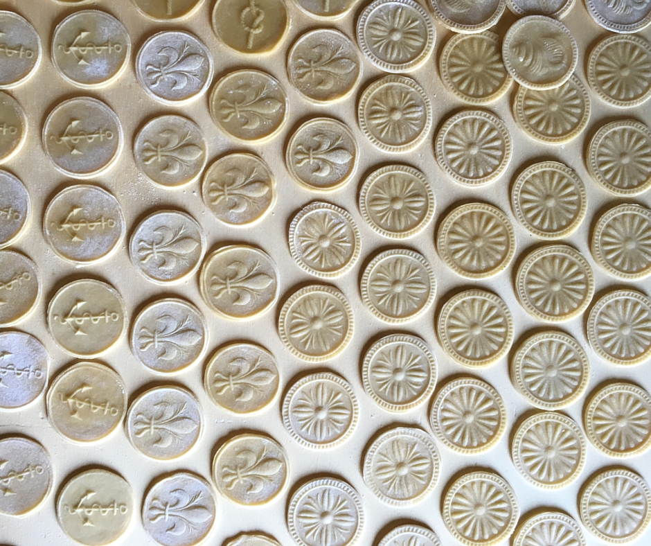 Corzetti pasta discs resting on wooden tray