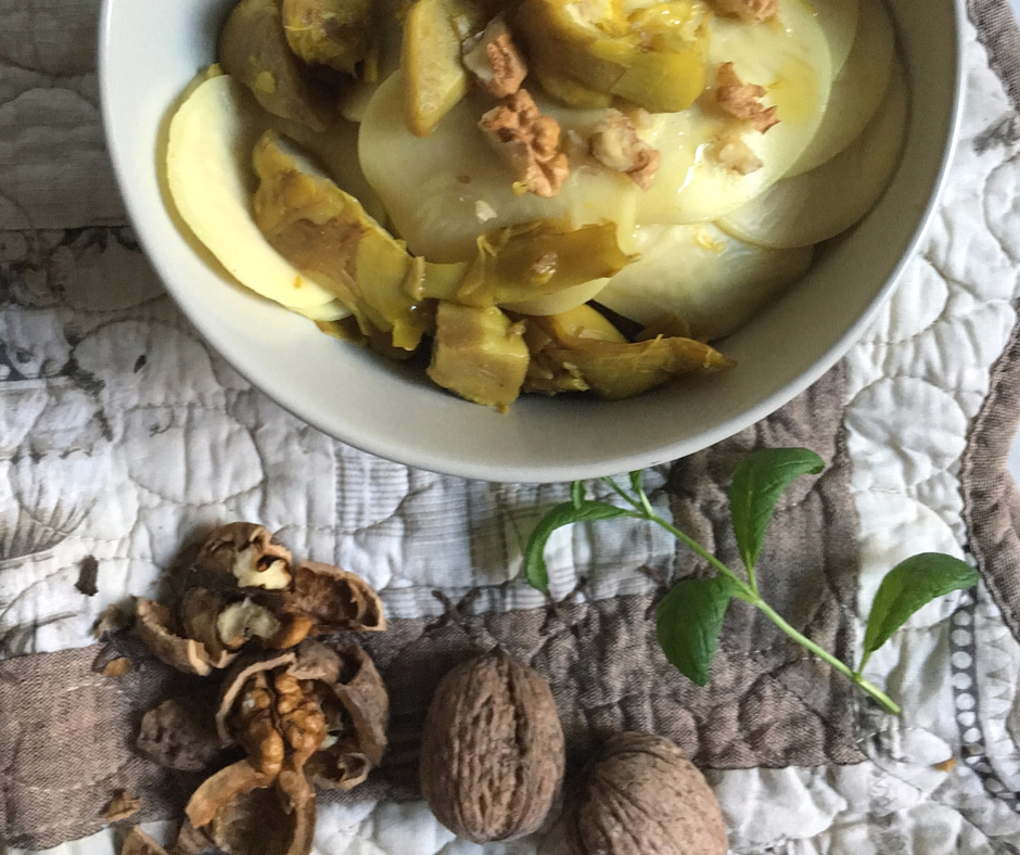 Bowl filled with corzetti pasta dressed with a sauce of artichocke, turmeric and walnuts